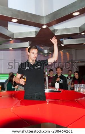 AMSTERDAM, NETHERLANDS - JUN 3, 2015: Unidentified barmen make glasses of Heineken at the Heineken Experience center. Gerard Adriaan Heineken was a founder of the Heineken beer - stock photo