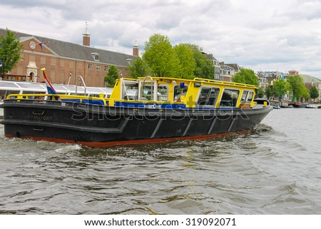 Amsterdam, Netherlands - June 20, 2015: Boats on a canal in Amsterdam. Netherlands - stock photo