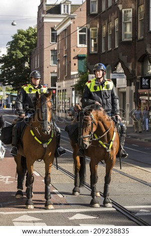 Amsterdam, Netherlands - June 29: Mounted police officers in Amsterdam, Netherlands on June 29, 2014.