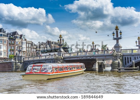 AMSTERDAM, NETHERLANDS - JUNE 16, 2013: The Blauwbrug (Blue Bridge) connecting the Rembrandtplein area with the Waterlooplein area. - stock photo