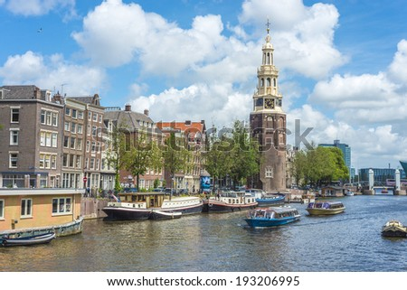 AMSTERDAM, NETHERLANDS - JUNE 16, 2013: The Montelbaanstoren tower on Oudeschans canal in Amsterdam, Netherlands, built in 1516 for the purpose of defending the city.