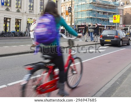 AMSTERDAM, NETHERLANDS - MARCH 18: a cyclist on March 18, 2015 in Amsterdam, Netherlands. Approximately 50% of journeys in Amsterdam are taken by bicycle and the city has 400km of cycle paths. - stock photo