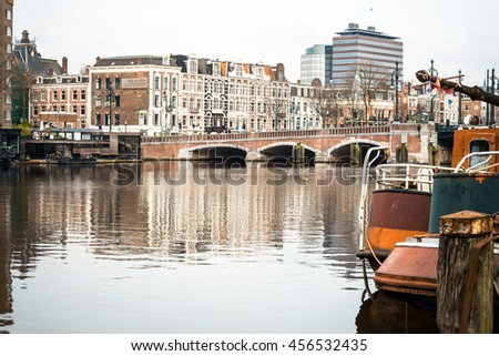 Amsterdam, Netherlands - March 31, 2016 : Beautiful view of Amsterdam canals with bridge and typical dutch houses. Amsterdam, Netherlands - stock photo