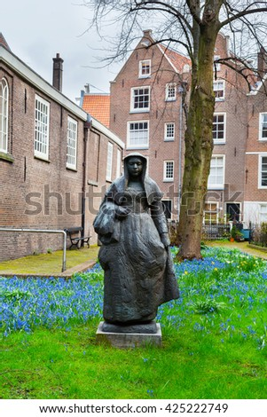 Amsterdam, Netherlands - March 31, 2016: Begijnhof courtyard with nun statue and garden surrounded by historic houses in Amsterdam, Netherlands - stock photo