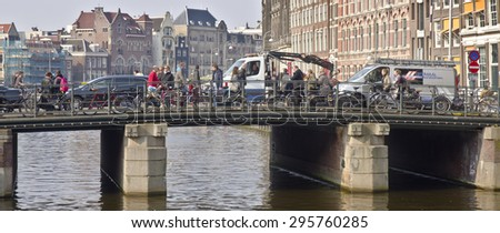 AMSTERDAM, NETHERLANDS - MARCH 18: bridge over canal on March 18, 2015 in Amsterdam, Netherlands. Amsterdam has more than one hundred kilometres of canals, and about 90 islands and 1,500 bridges. - stock photo