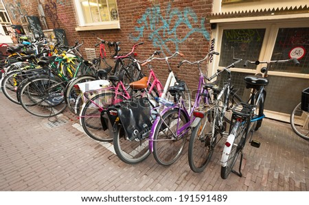 AMSTERDAM, NETHERLANDS - MARCH 19, 2014: Different bicycles stand on a parking place in Amsterdam