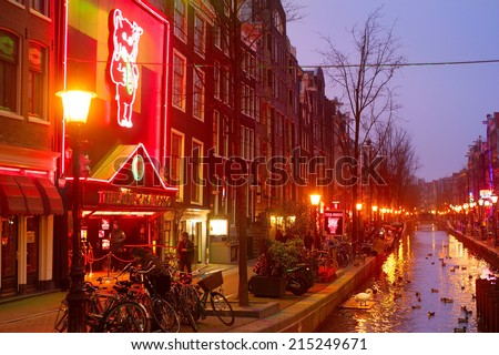 AMSTERDAM, NETHERLANDS - MARCH 10, 2013: Red-light district in Amsterdam. There are about three hundred cabins rented by prostitutes in the area.  - stock photo