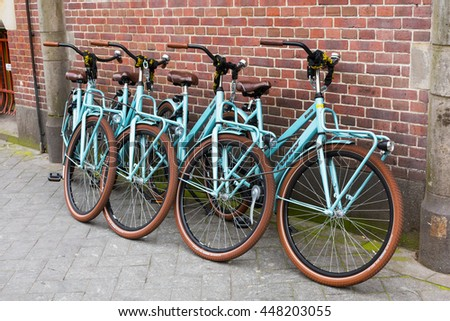 Amsterdam, Netherlands - March 31, 2016: Row of bikes for rent near brick wall in Amsterdam, Netherlands