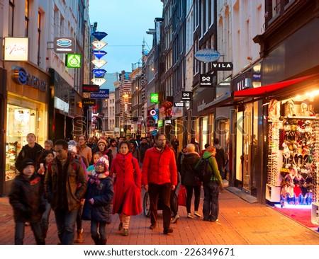 AMSTERDAM, NETHERLANDS - MARCH 01, 2014: Unidentified people walking on Kalverstraat - main shopping street of Amsterdam. The Kalverstraat is the most expensive shopping street in the Netherlands.  - stock photo