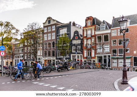 AMSTERDAM, NETHERLANDS - MAY 1, 2015:  Architecture on the Canal of Amsterdam in the evening. Amsterdam is the capital city and most populous city of the Kingdom of the Netherlands