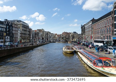 Amsterdam, Netherlands - May 7, 2015: Passenger boats on canal tour in the city of Amsterdam on May 7, 2015. Amsterdam is the capital and most populous city of the Netherlands. - stock photo