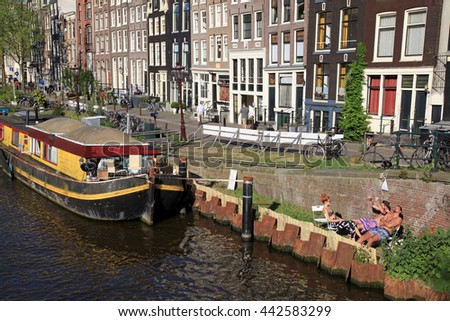 AMSTERDAM, NETHERLANDS - MAY 8, 2016: People relax on canal embankment near houseboat in Amsterdam,Netherlands. Houseboats are high demand very popular and common form of housing in Amsterdam - stock photo