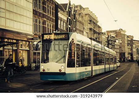 Amsterdam, Netherlands - May 13, 2015: The tram stop near Centraal station. Amsterdam Centraal station is the largest train station of Amsterdam and a major national rail hub with 260,000 passengers - stock photo