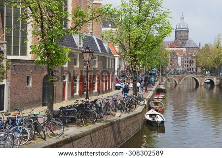 AMSTERDAM, NETHERLANDS - MAY 30, 2013: View to the canal with bicycles parked and basilica of Saint Nicholas at the background in Amsterdam, Netherlands. - stock photo