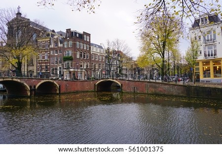 AMSTERDAM, NETHERLANDS -13 NOV 2016- Traditional Dutch row houses and house boats along canals in Amsterdam, the capital of the Netherlands.