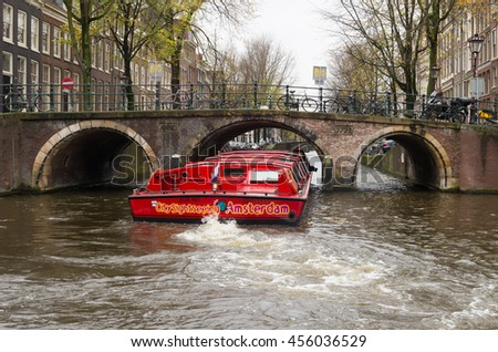 AMSTERDAM, NETHERLANDS - NOVEMBER 15, 2015: Red sightseeing boat sailing through the amsterdam canals. The city counts 165 canals.