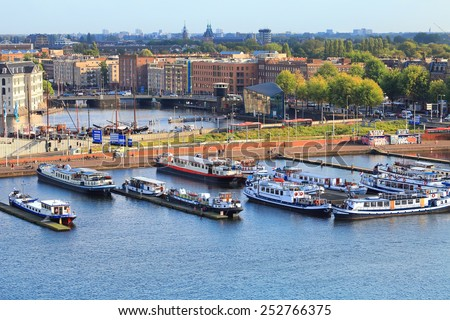 AMSTERDAM, NETHERLANDS - OCTOBER 09: Mooring of the tourist ships and urban view on Oosterdok in Amsterdam-Centrum. Netherlands, on October 09, 2014  - stock photo