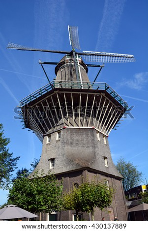 AMSTERDAM NETHERLANDS OCTOBER 01 2015: Nestled on the water at Zeeburgerdijk swings the huge blades of Amsterdam only windmill. But next door is the organic craft brew centre, Brouwerij 't IJ - stock photo