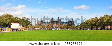 AMSTERDAM,NETHERLANDS - OCTOBER, 07:Park meadow view of National museum to arts and history (Rijksmuseum) of Netherlands and its beautiful Museum Square and public park Netherlands,on October 07,2014  - stock photo