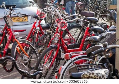 Amsterdam,Netherlands - October 31, 2015: Red Tourist Bicycles Parking at the city center in Amsterdam, Netherlands