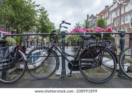 Amsterdam, Netherlands, on July 8, 2014. Bicycles are parked on the city street on the bank of the channel