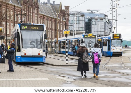 AMSTERDAM, NETHERLANDS on MARCH 28, 2016. Typical urban view in the spring afternoon. The tram moves down the street.