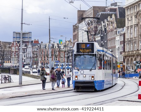 AMSTERDAM, NETHERLANDS on MARCH 29, 2016. Typical urban view in the spring afternoon. The tram moves down the street