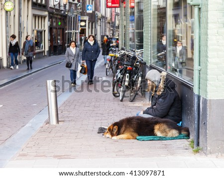 AMSTERDAM, NETHERLANDS on MARCH 28, 2016. Typical urban view in the spring evening. Homeless man with his dog in the street