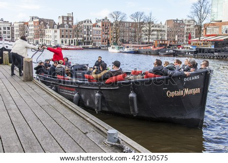 AMSTERDAM, NETHERLANDS on MARCH 27, 2016. Typical urban view. The walking ship with people and bar is onboard moored to the river bank Amstel