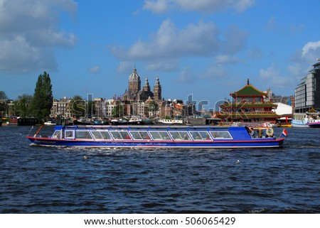 AMSTERDAM, NETHERLANDS - SEPTEMBER 22, 2011: Cruise ship with tourists sightseeing Amsterdam panorama. Canal trips in beautiful dutch capital city is very popular between tourists.