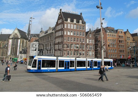 AMSTERDAM, NETHERLANDS - SEPTEMBER 22, 2011: Tram car on Dam Square or Dam. Dam is famous town square with many tourist attractions in Amsterdam.