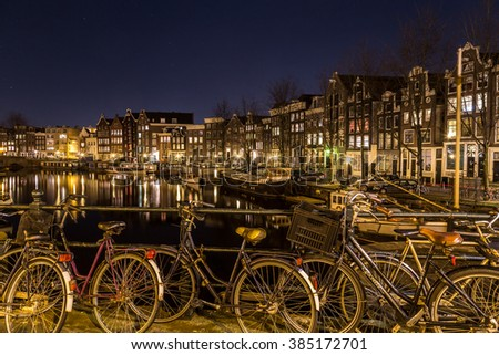 AMSTERDAM, NETHERLANDS - 16TH FEBRUARY 2016: A view along the Waalseilandgracht Canal in Amsterdam at night with bikes in the foreground. - stock photo