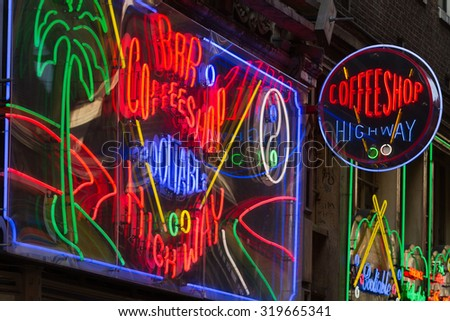 AMSTERDAM - OCT 31: Night image of colorful coffee shop signs in the red district on October 31, 2011, in Amsterdam, the Netherlands. It is probably the most famous tourist site in town. - stock photo