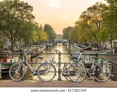 AMSTERDAM - OCTOBER 3: City scene of Amsterdam in evening twilight time along canal, bride and bicycles, Netherlands, on October 3, 2015.