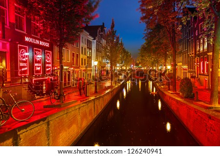 AMSTERDAM - OCTOBER 1 2012: Red-light district in Amsterdam on October 1 2012 in Amsterdam, Netherlands. There are about three hundred cabins rented by prostitutes in the area. - stock photo
