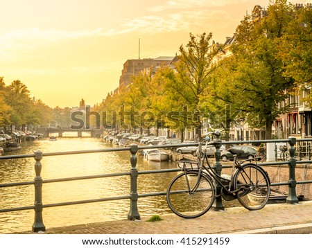 AMSTERDAM - OCTOBER 3: Twilight evening city scene of Amsterdam with bicycle and transportation along canal in Netherlands, on October 3, 2015.