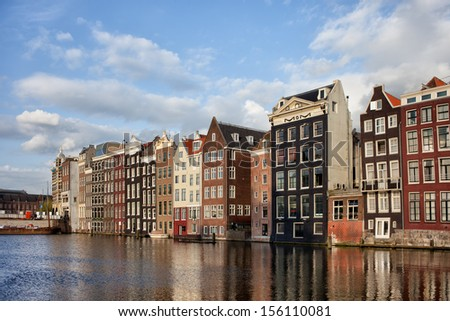 Amsterdam Old Town at sunset in Netherlands, terraced Dutch style historic houses with reflections on water.