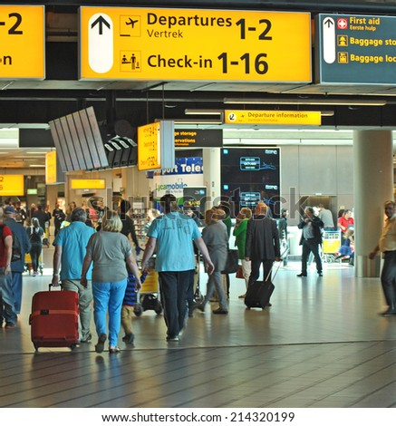 AMSTERDAM/SCHIPHOL, THE NETHERLANDS, 27 AUGUST 2014 - Dutch passengers passing a sign on Amsterdam Airport Schiphol. - stock photo