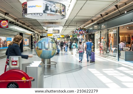 AMSTERDAM SCHIPHOL, THE NETHERLANDS - AUGUST 10, 2014: People shopping at the designer outlet shopping center Schiphol plaza at Schiphol airport, Amsterdam on august 10, 2014. - stock photo