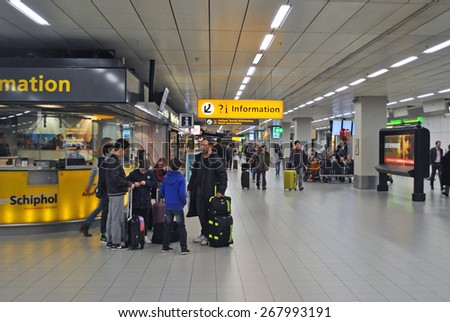 AMSTERDAM/SCHIPHOL, THE NETHERLANDS, 26 MARCH 2015 - Airplane passengers waiting at an information point on Amsterdam Airport Schiphol. - stock photo