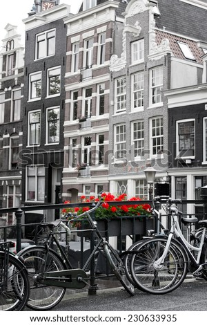 Amsterdam street scene with old bicycles against a backdrop of traditional Merchant houses. Black and white with selective colouring on flowers.  - stock photo