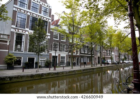 AMSTERDAM; THE NETHERLANDS - AUGUST 18; 2015: View on beautiful street Oudezijds Achterburgwal, street life, canal and tourists. Amsterdam is capital of the Netherlands on August 18; 2015.