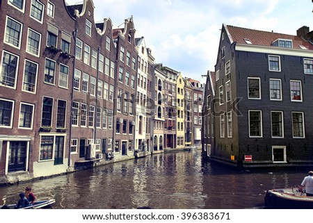 AMSTERDAM, THE NETHERLANDS - AUGUST 19, 2015: View on Oudezijds Kolk canal, street life, bicycle, canal in Amsterdam. Amsterdam is capital of the Netherlands on August 19, 2015. - stock photo