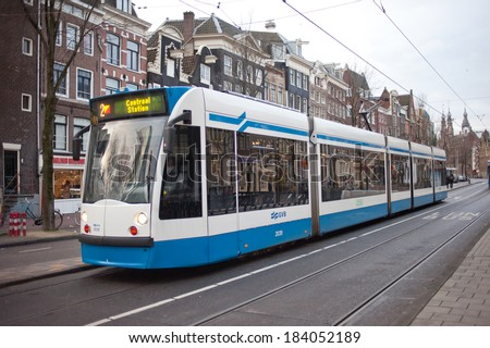 Amsterdam, The Netherlands - January 4, 2014: A tram (rail vehicle which runs on tracks along public urban streets) next to dam square, Amsterdam, The Netherlands