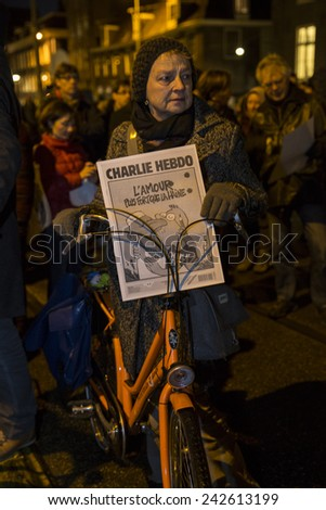 """Amsterdam, The Netherlands, January 8 2015: demonstation in solidarity with Charlie Hebdo in Paris, France on 07/01/2015. A woman holds an issue of Charlie Heddo saying """"love is stronger than hate"""" - stock photo"""