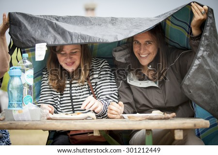 Amsterdam, The Netherlands - July, 5 2015: 2 young woman having lunch under the rain during Amsterdam Roots Open Air, a cultural festival held in Park Frankendael on 05/07/2015