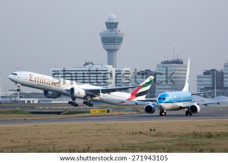 AMSTERDAM, THE NETHERLANDS--17 JUNE 2014-- A Emirates Boeing B777 is taking off from the runway.  - stock photo