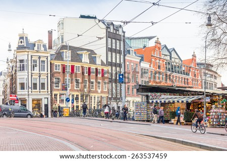 AMSTERDAM, THE NETHERLANDS - MARCH 7, 2015: People walking in the famous flower market, March 7, 2015 in Amsterdam, The Netherlands. Founded in 1862, it's the only floating flower market in the world. - stock photo
