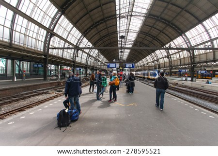 Amsterdam, The Netherlands - May 1, 2015: People and Intercity Train parked at Amsterdam Centraal station.  - stock photo