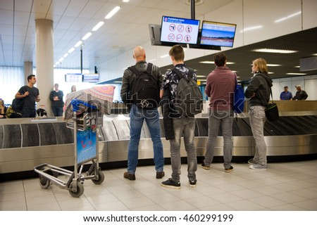 AMSTERDAM, THE NETHERLANDS - MAY 05, 2016: People are waiting on an airport at the luggage belt for their suitcases to arrive.